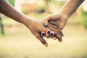 Two people holding hands. Having someone be there for you can help reduce anxiety