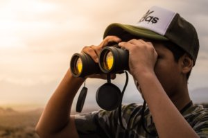 A man looking through binoculars to find volunteer activities