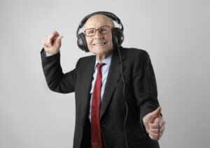 An older man wearing headphones and smiling because he is enjoying his podcast