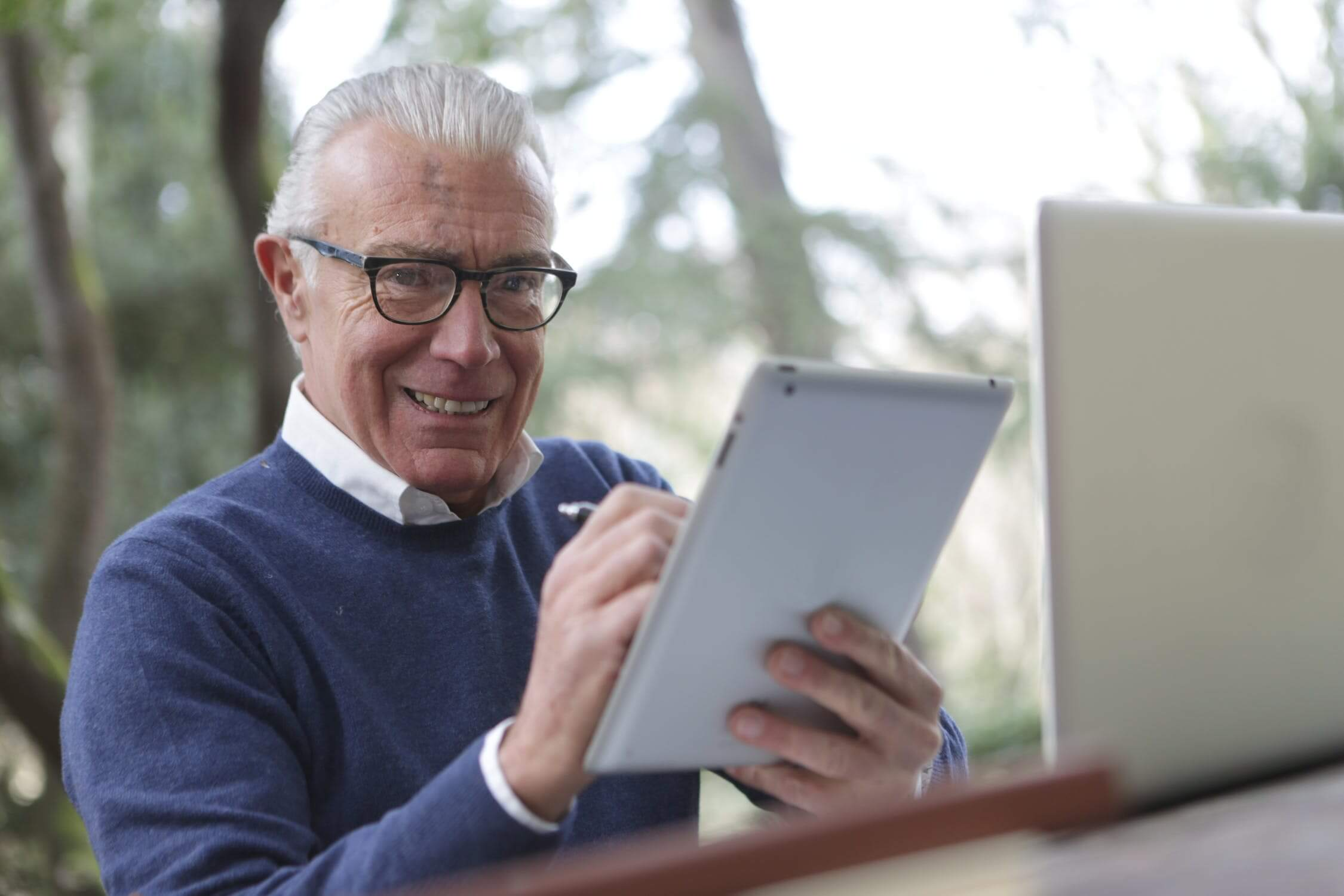 An older man using an ipad to stay connected with loved ones in quarantine