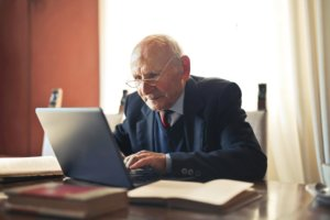 An older man using his laptop to help his grandchildren with homework during quarantine