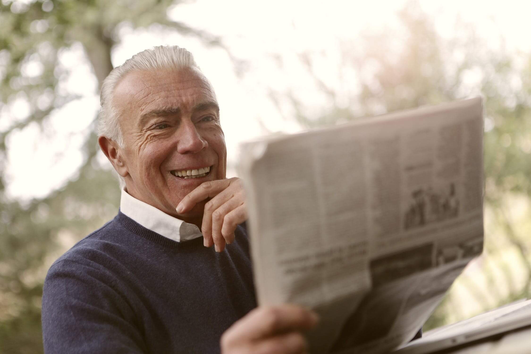 A man smiling while reading the newspaper