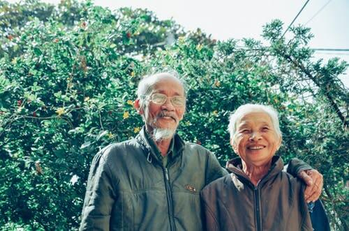 An elderly couple outside smiling