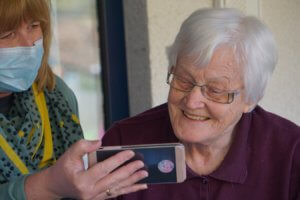 An older woman playing a phone game