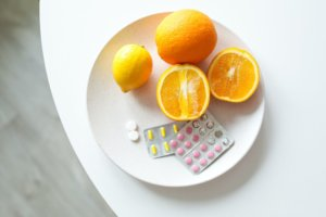 Vitamins on a plate with oranges