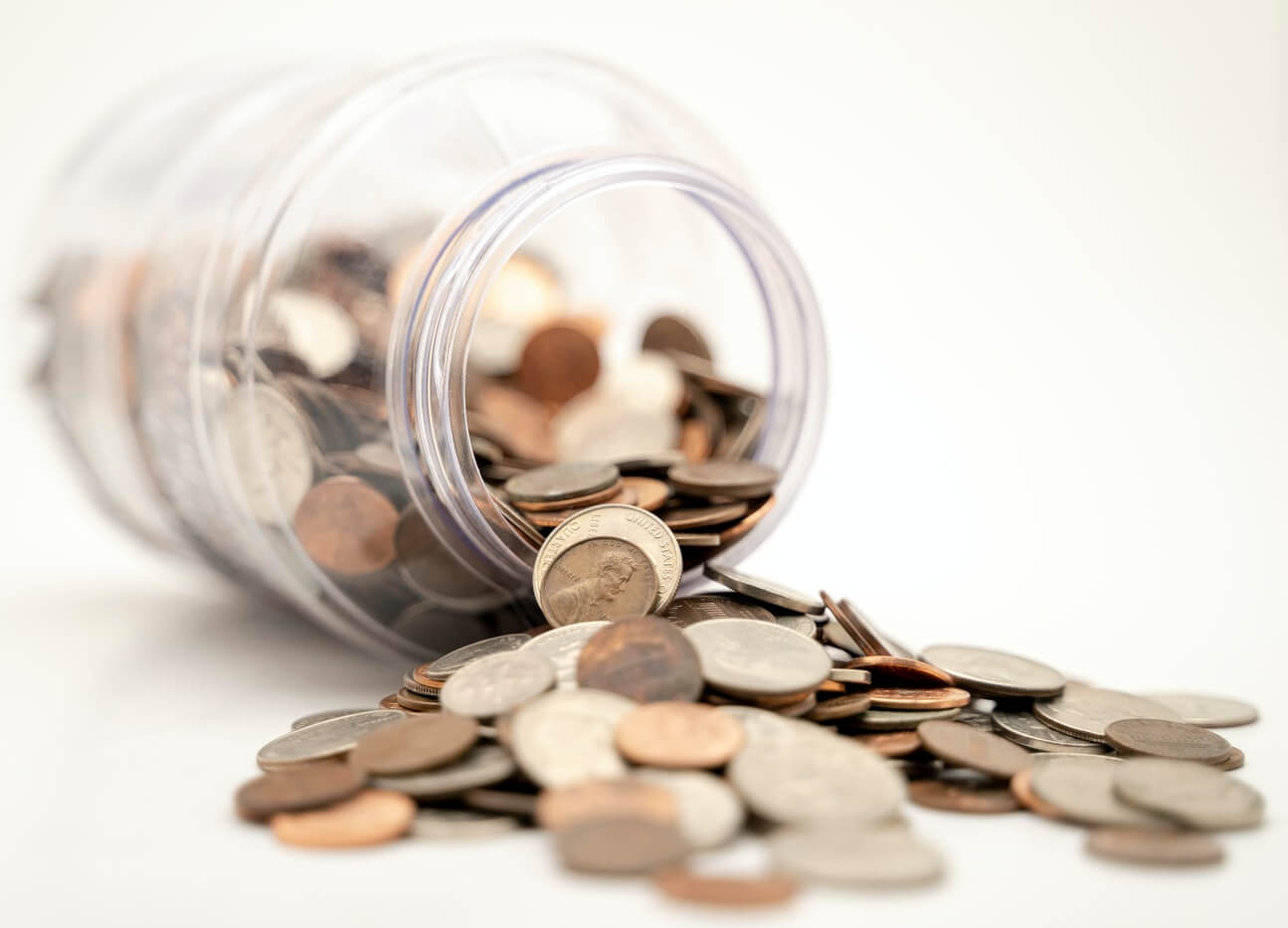A jar holding different coins. It is important to save money for retirement