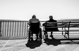 An older couple sitting near the beach wondering if they need dementia care