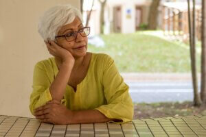 An older woman thinking outside about senior scams she should be aware of